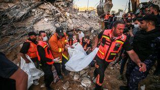 Des secouristes palestiniens évacuent un blessé après le bombardement d'un immeuble à Beit Lahia, le 13 mai 2021, dans la bande de Gaza. (MUSTAFA HASSONA / AFP)