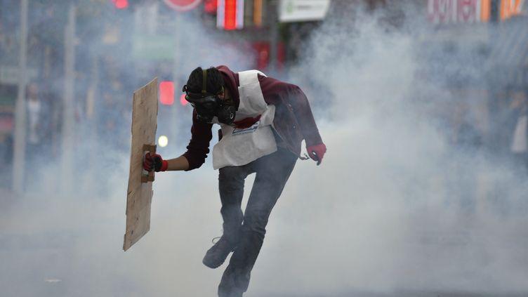 Un manifestant se protège des gaz lacrymogène tirés par les forces de l'ordre, à Ankara (Turquie), le 15 mai 2014. (REUTERS)