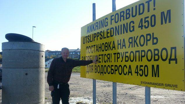 """(Bernt Nilsen devant un panneau qui dit """"interdiction de jeter l'ancre"""" (car le pipeline de la mine sort à cet endroit du fjord) © Benjamin Illy / RF)"""