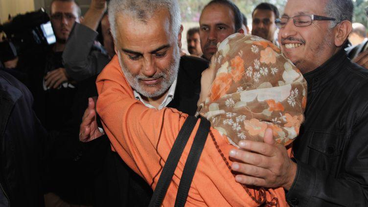 Le chef du Parti de la justice et du développement, Abdelilah Benkirane, félicité par une militante au siège du parti, le 26 novembre 2011 à Rabat (Maroc). (YOUSSEF BOUDLAL / REUTERS)
