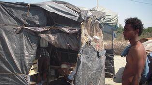 Fathi, un jeune réfugié soudanais, mercredi 1er juillet à Calais (Pas-de-Calais), devant la tente où il partage une cuisine avec une quinzaine d'autres migrants. (LOUIS BOY / FRANCETV INFO)