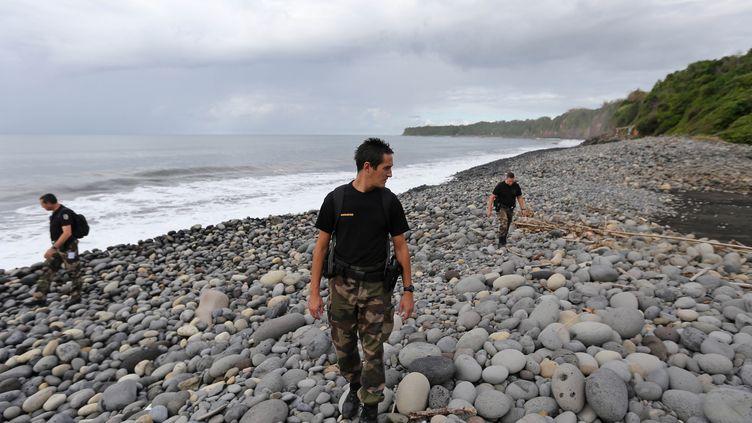 Des officiers de la gendarmerie à la recherche de débris éventuels du vol MH370 de la Malaysia Airlines, sur une plage de Sainte-Marie de la Réunion (La Réunion), le 8 août 2015. (RICHARD BOUHET / AFP)