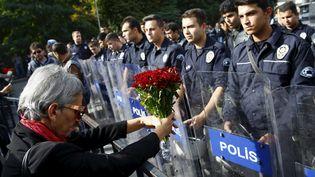 Une manifestante tendant des fleurs aux policiers chargés d'encadrer la manifestation à Ankara (Turquie), le 11 octobre 2015. ( UMIT BEKTAS / REUTERS)