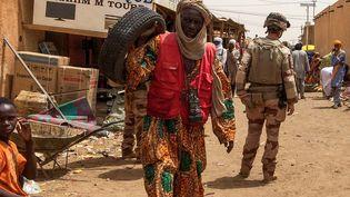 De dos, soldat français de l'opération Barkhane sur le marché de Menaka,au nord-est du Mali. Dans cette ville, non loin de la frontière avec le Niger, des ONG françaises remettent en fonctionnement l'eau, l'electricité. Photo prise le 27 juin 2019. (MARIE WOLFROM / AFP)