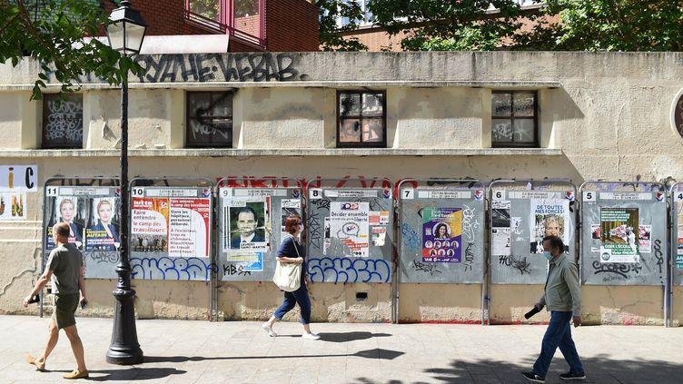 Des passants devant des affiches électorales à côté d'un bureau de vote à Paris, lors du premier tour des élections régionales. (Illustration, le 20 juin 2021). (LUCAS BARIOULET / AFP)