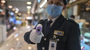 Un policier chinois avec un thermomètre, le 21 mars 2020 à Shanghai (Chine). (HECTOR RETAMAL / AFP)