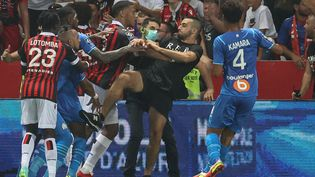 Un supporter de l'OGC Nice tente de frapper Dimitri Payet pendant le match entre Nice et Marseille à l'Allianz Riviera, le 23 août. (VALERY HACHE / AFP)