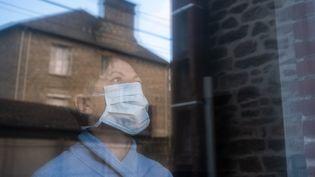 Une femmeregarde dehors depuis chez elle, le 16 mars 2020, à Dinan (Côtes-d'Armor). (MARTIN BERTRAND / HANS LUCAS / AFP)