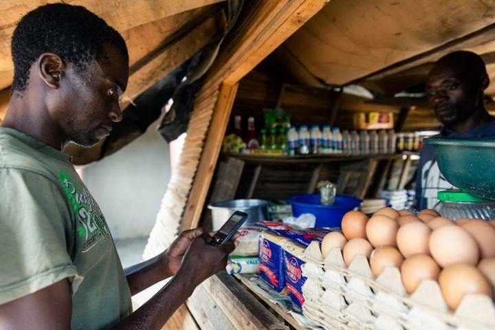 Payer ses menus achats par téléphone devient une pratique de plus en plus fréquente en Afrique comme ici à Harare, la capitale du Zimbabwe, en décembre 2019. (JEKESAI NJIKIZANA / AFP)