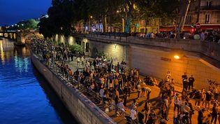 Des Parisiens réunis sur les quais de Seine à l'occasion de la fête de la musique le 21 juin 2021. (BORIS LOUMAGNE / RADIO FRANCE)