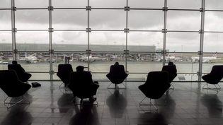 Des voyageurs attendent leur avion au terminal 2E, à l'aéroport de Roissy-Charles de Gaulle, le 18 mars 2021. (ERIC PIERMONT / AFP)