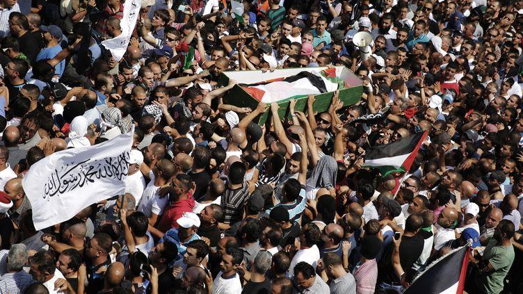 La foule transporte le cercueil de l'adolescent palestinien assassiné, le 4 juillet 2014, dans un quartier de Jérusalem-Est. (FINBARR O'REILLY / REUTERS)