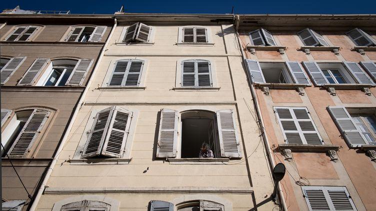 Une femme regarde par la fenêtre de son appartement, rue d'Aubagne à Marseille, le 18 novembre 2018, près de l'endroit où deux immeubles se sont effondrés. (GERARD JULIEN / AFP)