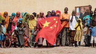 Le 4 juillet 2018 à Djibouti, sous le portrait du président Ismaël Omar Guelleh, la foule agite un drapeau chinois lors dela pose de la première pierre d'un complexe de 1 000 logements financé par la Chine. (YASUYOSHI CHIBA / AFP)