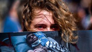 Une manifestante de l'opposition biélorusse tient la photo d'un homme blessé lors de la contestation contre Loukachenko. (SERGEI GAPON / AFP)