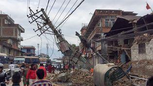 Des personnes dans les rues de Katmandou face aux ruines de bâtiments mis à terre par le séisme qui a frappé le Népal, samedi 25 avril 2015. (ARNE ADRIAN / DPA / AFP)