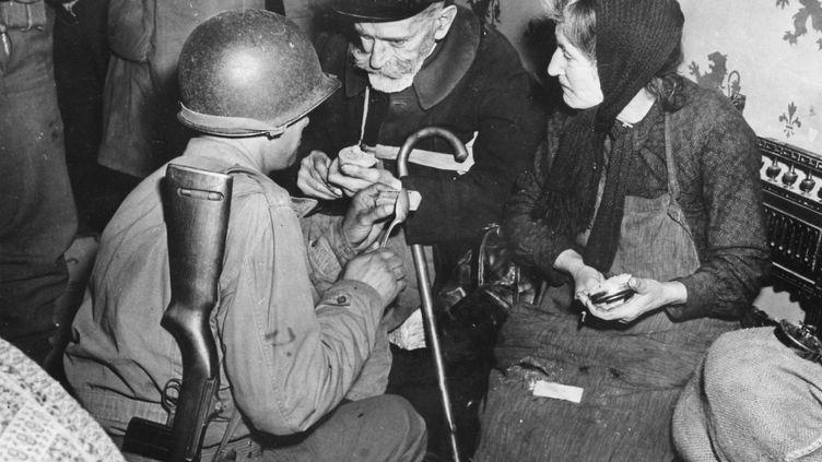 Un soldat américain donne du chocolat à un couple, en juin 1944, à La Haye-du-Puits (Manche). (COLL-DITE / AFP)