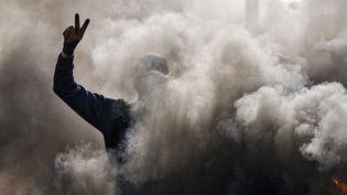 Un manifestant anti-gouvernement fait le V de la victoire à travers la fumée de pneus enflammés lors d'une manifestation le 26 janvier 2020sur la route de l'aéroport international de Najaf, à 160 km ausud de Bagdad. (HAIDAR HAMDANI / AFP)