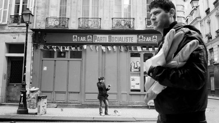 Un homme passe devant un bureau du Parti socialiste, le 5 mai 2012, à Paris. (ERIC FEFERBERG / AFP)