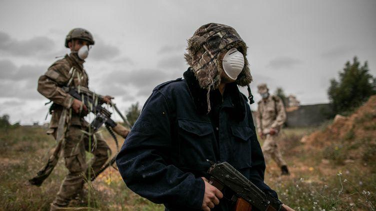 Les forces du gouvernement d'union nationale, opposéesà celles du chef de guerre Khalifa Haftar, portent des masques pour se protéger du coronavirus, à Tripoli le 25 mars 2020. (AMRU SALAHUDDIEN / ANADOLU AGENCY)