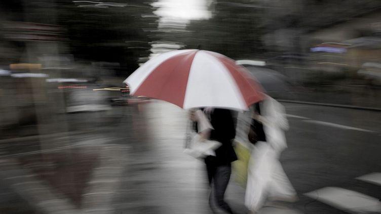 Des passants marchent sous une averse, le 10 juin 2008 à Dijon (Côte d'Or). (JEFF PACHOUD / AFP)