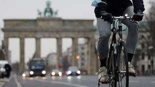Un cycliste pédale sur la piste cyclable près de l'emblématique porte de Brandenburger, dans le centre de Berlin (Allemagne), le 7 décembre 2020. (ODD ANDERSEN / AFP)