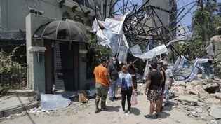 Des habitants de Beyrouth devant les gravats après l'explosion, le 5 août 2020. (JOSEPH EID / AFP)
