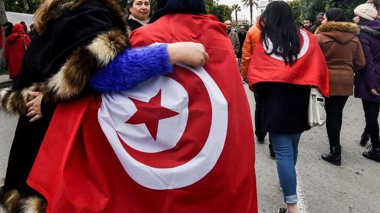 Des Tunisiennes défilent avec le drapeau national, lors d'un rassemblement sur l'avenue Habib Bourguiba à Tunis, le 14 janvier 2017, quimarque le 6e anniversaire de la révolution 2011. (FETHI BELAID / AFP)