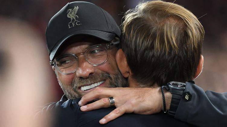L'entraîneur de Liverpool, Jürgen Klopp (à gauche), embrasse son homologue du PSG, Thomas Tuchel, lors de la confrontation entre les deux clubs, en Angleterre, le 18 septembre 2018. (PAUL ELLIS / AFP)