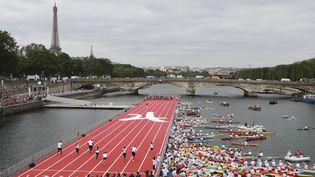 Paris a installé sur la Seine, le 23 juin 2017, une piste d'athlétisme pourcélébrer la journée qui marque la création du Comité international olympique par Pierre de Coubertin le 23 juin 1894. (JACQUES DEMARTHON / AFP)