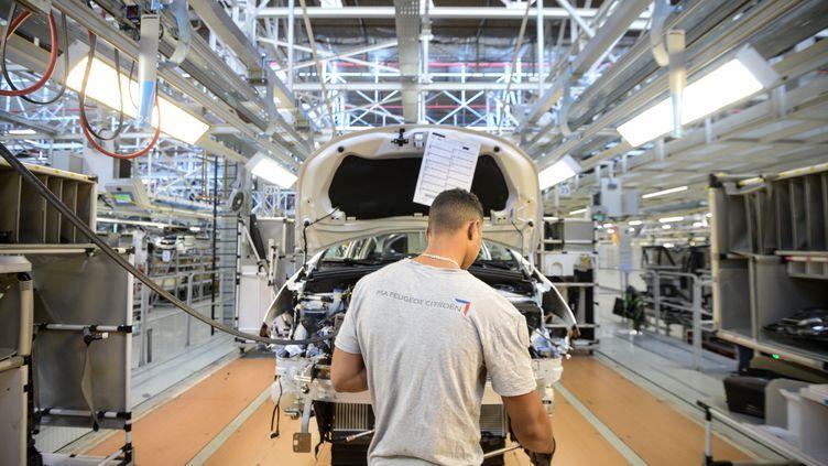 Un employé de PSA dans une usine de Mulhouse (Haut-Rhin), en 2017. Photo d'illustration. (SEBASTIEN BOZON / AFP)