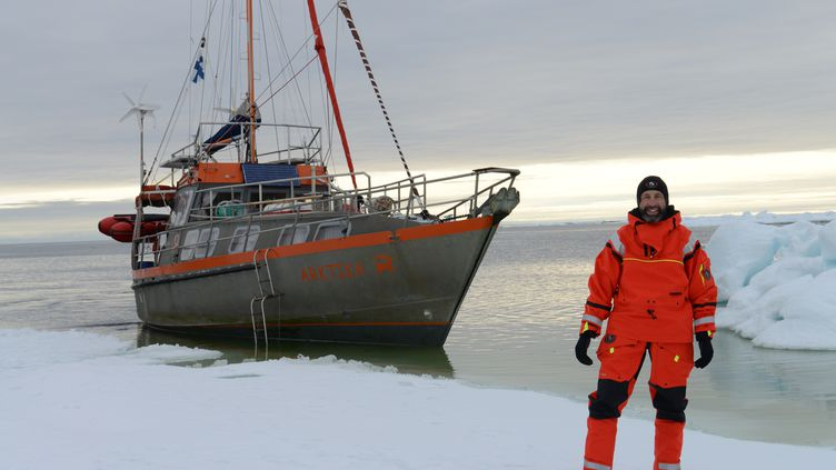 "Gilles Elkaim pose devant son navire, ""Arktika"", en mer de Kara, au nord de la Russie, en 2014. (GILLES ELKAIM / FRANCEINFO)"