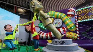 """Un char du carnaval de Cologne représente une statue d'Emmanuel Macron déboulonnée par des """"gilets jaunes"""", le 26 février 2019. (OLIVER BERG / DPA / AFP)"""
