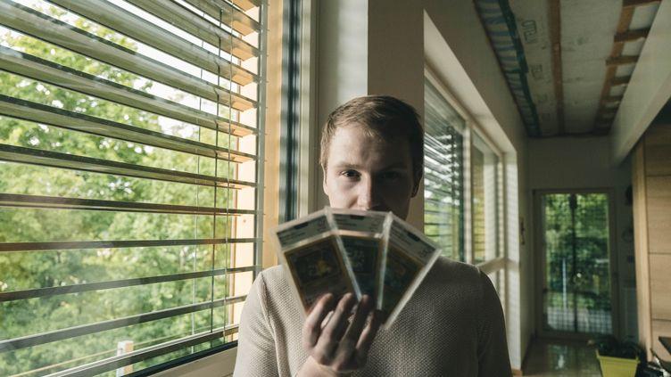 Pierre Louis, aka PricePokemon, collectionne des cartesPokémondepuis 5 ans, dans ses mains un Dracaufeu première édition. (MATTHIEU BONHOURE / RADIO FRANCE)