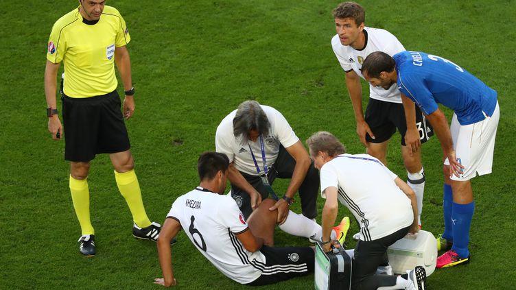 Klaus Eder (de dos), au chevet deSami Khedira, le 2 juillet, lors du quart de finale entre l'Allemagne et l'Italie. (CHRISTIAN CHARISIUS / DPA / AFP)