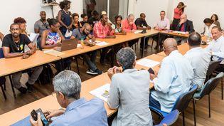 Des représentants du collectif Pou Lagwiyann Dekolé, des élus et le préfet de Guyane, réunis pour passer en revue les élements de l'accord finalement signé le 21 avril 2017 à Cayenne (JODY AMIET / AFP)