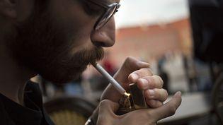 Un homme allumant une cigarette (illustration) (MACIEJ LUCZNIEWSKI / NURPHOTO / AFP)