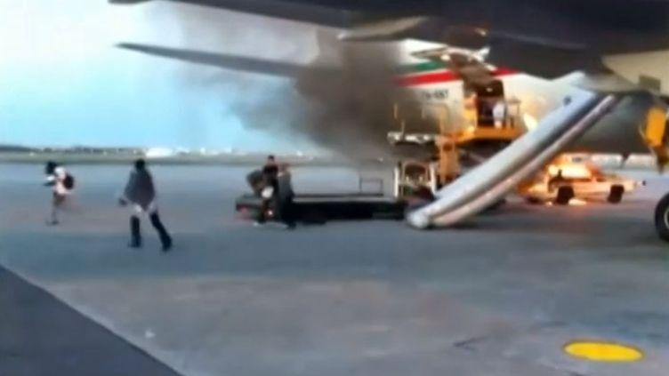 Des passagers d'un avion de la Royal Air Maroc évacuent un appareil en feu, le 4 novembre 2013, à l'aéroport de Montréal (Canada). ( FRANCE 2 / FRANCETV INFO)