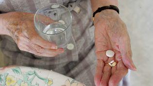 Une personne âgée prend des médicaments, le 28 juin 2005, dans une maison de retraite à Lorient (Morbihan). (MAXPPP)