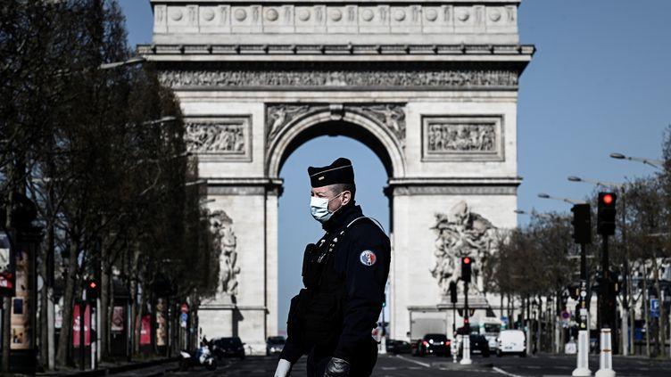 Un policier portant un masque, lors d'une opération de contrôle sur les Champs-Elysées, à Paris, le 23 mars 2020. Photo d'illustration. (PHILIPPE LOPEZ / AFP)
