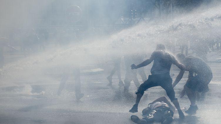 """Un manifestant à terre le 14 septembre 2019 à Nantes, après l'utilisation d'un canon à eau par les forces de l'ordre, lorsd'une manifestation des """"gilets jaunes"""". (SEBASTIEN SALOM-GOMIS / AFP)"""