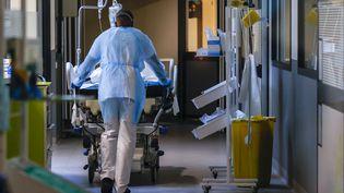 Un patient malade duCovid-19 est transporté par un brancardier dans un service de soins intensifs de l'hôpital Delafontaine à Saint-Denis(Île-de-France), le 29 mars 2021. (THOMAS SAMSON / AFP)