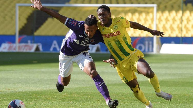 Le défenseur toulousain Kelvin Amian à la lutte avec le Nantais Charles Traoré, le 30 mai 2021. (SEBASTIEN SALOM-GOMIS / AFP)