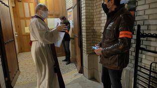 Des agents de sécurité s'assurent que seulement 30 personnes pénètrent dans une église parisienne à l'heure de la messe, le 28 novembre 2020. (PHILIPPE LAVIEILLE / MAXPPP)