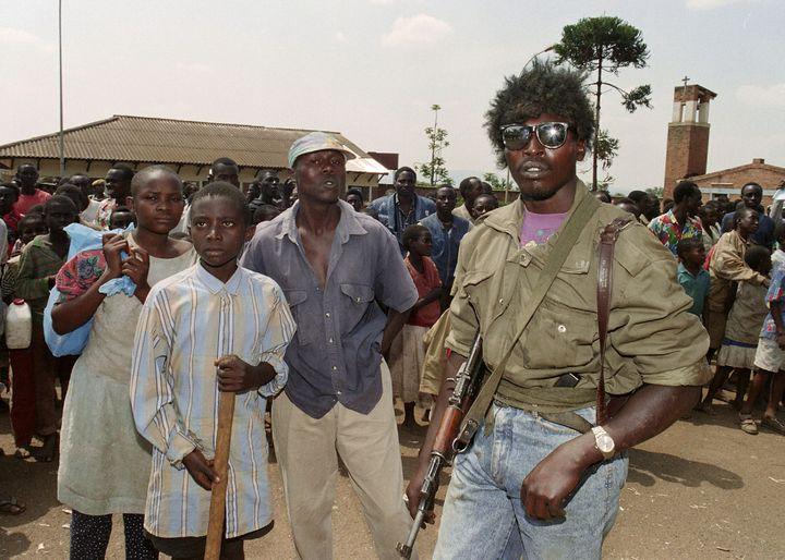 Des miliciens hutus assistent à l'évacuation, par les Nations unies, de 400 Tutsis de l'église de la Sainte-Famille, à Kigali,le 13 juin 1994. (ABDELHAK SENNA / AFP)