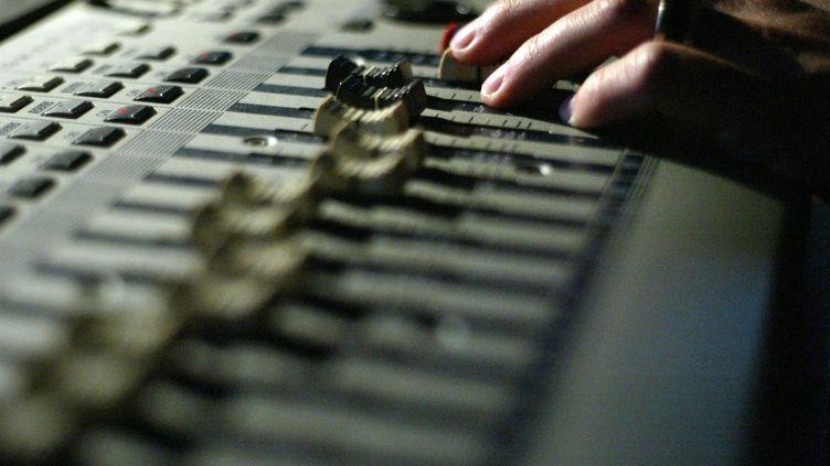 Un ingénieur du son travaille sur une table de mixage, dans un studio d'enregistrement (illustration). (MARTIN BUREAU / AFP)
