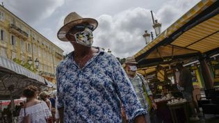 Un homme porte un masque sur un marché de Nice, le 3 août. (VALERY HACHE / AFP)