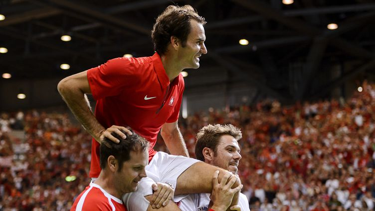 Roger Federer, ici porté par son capitaine Severin Luthi et Stan Wawrinka  (FABRICE COFFRINI / AFP)