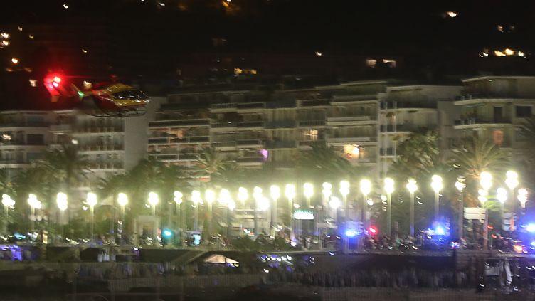 Un hélicoptère survole le site où un camion a foncé dans la foule sur la Promenade des Anglais à Nice (Alpes-Maritimes), le 14 juillet 2016. (VALERY HACHE / AFP)