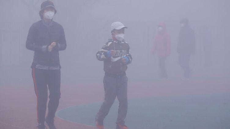 Des piétons portent des masques contre l'air pollué à Dalian (Chine), le 6 mars 2019. (LIU DEBIN / IMAGINECHINA / AFP)
